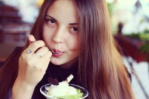 young beautiful woman eating a dessert of kiwi